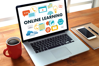 Photo of laptop with Online Learning sitting on a desk